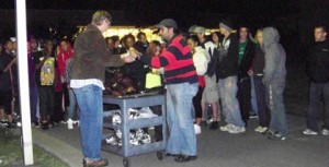 A crowd gathers as the roasted pig is cut. photo by Britteny Whatley