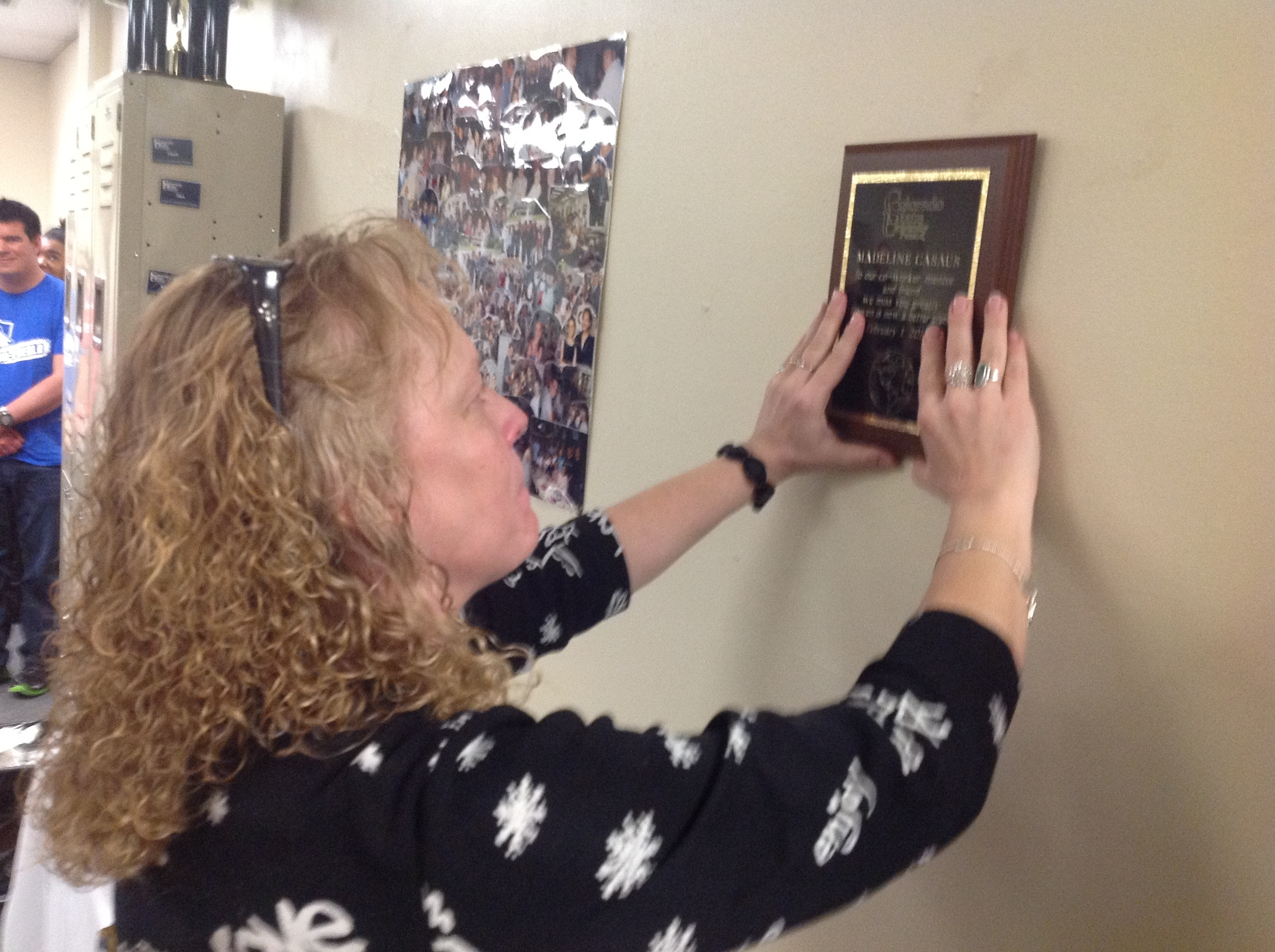 Director of Center for International Progrms, Annie Williams, placing Madeline Casis's plaque on the wall of new international students' lounge. Photo courtesy of Talha Qureshi