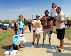 A Residence Life and Housing employee and CSU-Pueblo football players help a freshman move in as his mother watches. Photo by Michelle Pham.